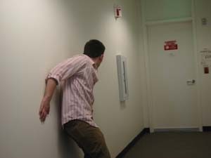 Office worker sidles along the wall of an office hallway - photo from original article